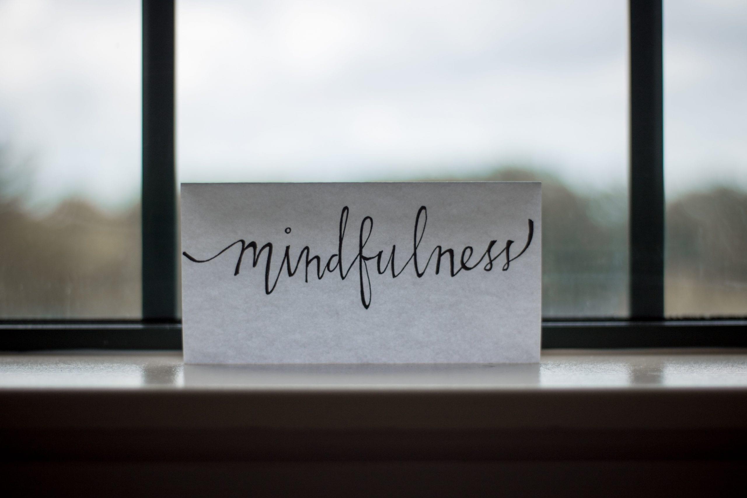 Scritta su foglio appoggiato a un davanzale: la parola è mindfulness, una pratica di meditazione