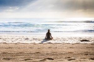 donna in riva al mare che pratica mindfulness